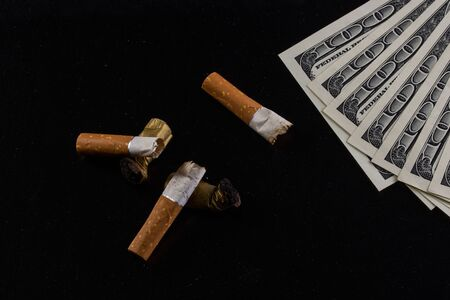 different cigarette butts nasty and charred lie on a dark background next to the dollar bills concept of the financial cost of the drug