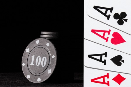 black poker chips on a dark background and a bright combination of four aces the concept of gambling and casino Standard-Bild - 114162482