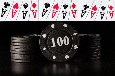 columns of black poker chips on a dark background and combinations of four aces casino concept Standard-Bild - 114162488