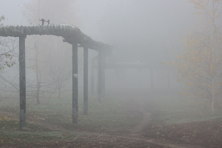 gas pipeline goes into the thick mysterious fog mystical cityscape nobody around the concept of autumn