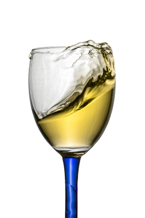 Powerful splash of white wine in a transparent glass with a bright blue leg Object for design Concept of alcoholic beverages 免版税图像