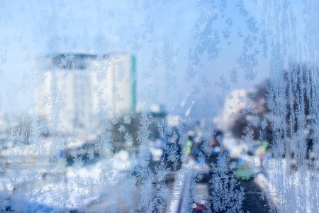 blue ice patterns on frozen glass on a blurred background of a tall building and cars passing on the road concept of nature and the cold season Stock fotó