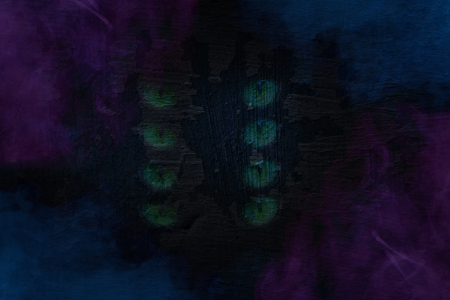 concrete grunge texture of an old building wall with mystical patterns in the form of four pairs of green cat eyes mysterious clouds of blue and violet cigarette vapor around the edges background for design