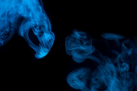 mystical blue patterns of cigarette vapor on a dark background bright and mysterious abstraction for design concept of smoking 写真素材
