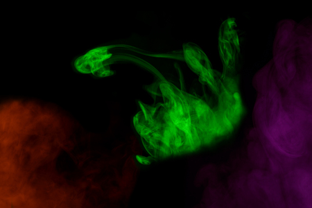 green mystical pattern of cigarette vapor resembling a snake close-up on a dark background abstraction for design concept of smoking