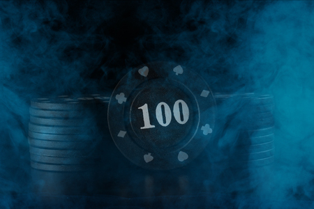 black poker chips in a hazy cigarette vapor close up business and casino concept 版權商用圖片