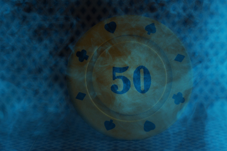 poker chip round and plastic closeup in blue cigarette smoke concept of gambling and casino
