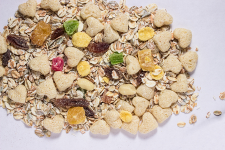 raw muesli lie on a gray sheet of paper close-up various bright ingredients oat flakes candied raisins and corn flakes concept of healthy eating and vegetarianism
