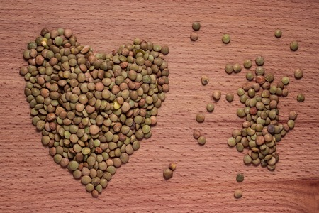 bright heart lined with cereal lentils on a wooden background close-up concept of food and vegetarianism Stok Fotoğraf
