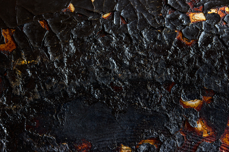 black texture of burnt and cracked metal on the surface of the frying pan close-up exciting patterns grunge background for design