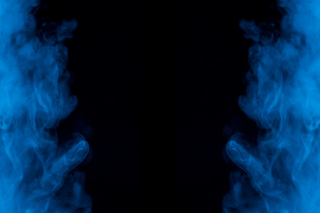 symmetrical two clouds of blue cigarette vapor on a dark background exciting patterns background for design 写真素材