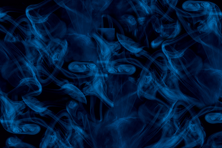 charming ghostly patterns formed by blue cigarette vapor on a dark background abstraction for design concept of smoking Imagens