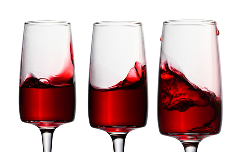 three beautiful splashes of red wine in elegant glasses on a white background concept of alcohol Stock fotó