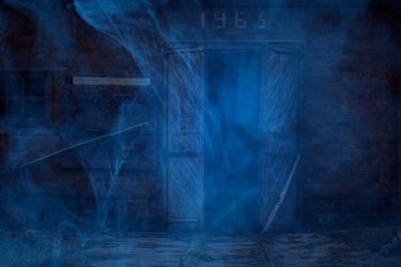 night facade of an old brick building with wooden doors covered with blue ghostly mist concept of mystique and halloween
