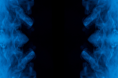 clouds of blue cigarette vapor with bewitching mystical patterns on a dark background exciting abstraction for design concept of halloween and mystery 写真素材