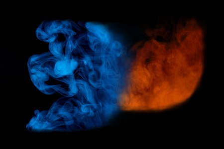 blue and orange cigarette vapor came together in a bewitching cloud against a dark background colored smoking concept