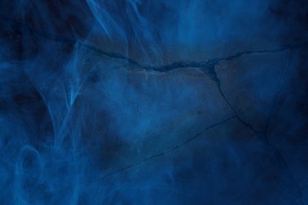 Mysterious stone texture with wide dark cracks covered in ghostly blue fog Halloween concept Abstraction for design