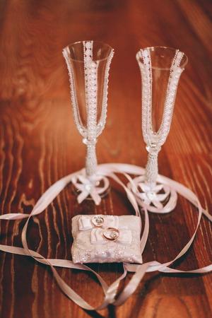 white  wedding: luxury wedding rings with stylish decoration near them.
