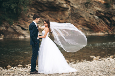 honeymooners: Elegant gentle stylishElegant gentle stylish groom and bride near river with stones. Wedding couple in love. Stock Photo