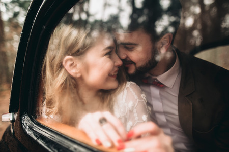 Romantic fairytale wedding couple, bride and groom, kissing and embracing in pine forest near retro car.