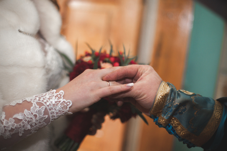 fingers put together: Newlyweds in dress wedding wear ring in the church.