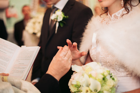 fingers put together: Newlyweds dress wedding ring in the church. Stock Photo