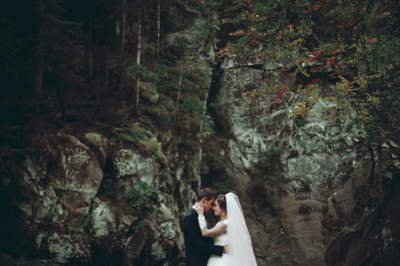 stay beautiful: Beautiful wedding couple stay on stone of the river in scenic mountains.