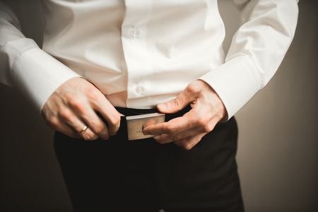 cuff link: Gorgeous man, groom prepares for wedding ceremony in luxury hotel. Stock Photo