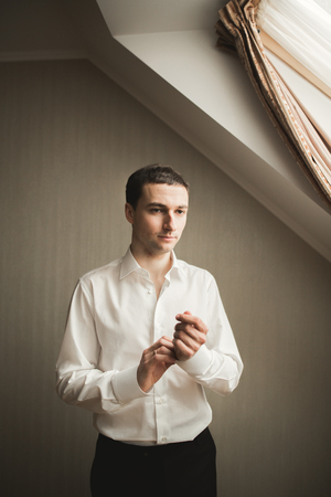 young  cuffs: Gorgeous man, groom prepares for wedding ceremony in luxury hotel. Stock Photo
