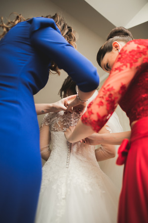 getting a bride: Happy buddies helps bride getting ready for her wedding day in the morning.