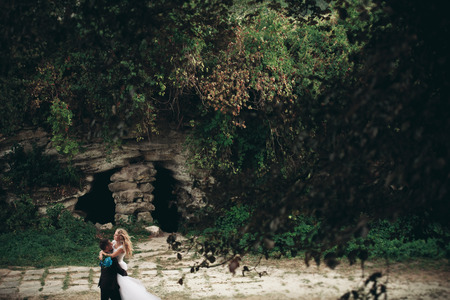 Luxury wedding couple hugging on the background gorgeous plants and cave near ancient castle.