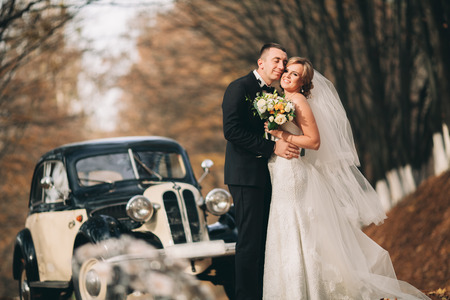 married couples: Stylish wedding couple, bride and groom hugging near retro car in autumn.