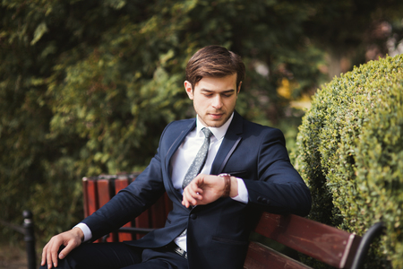 Confident businessman looking on his wrist watch in suit. 免版税图像