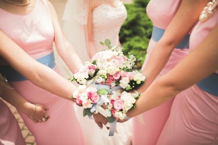 신부 및 신부 들러리는 그들의 손에 아름다운 꽃을 보이고있다.