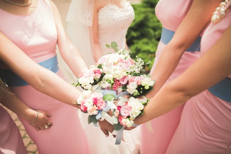 The bride and bridesmaids are showing beautiful flowers on their hands. Stock Photo