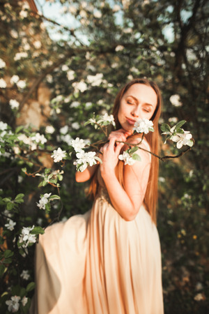 Young beautiful girl in a long dress and a wreath of flowers in the garden of lilac bush.