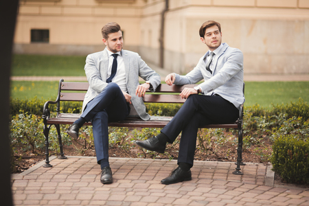 swivel chairs: Two stylish businessmen speaking and smiling outdoors. Stock Photo