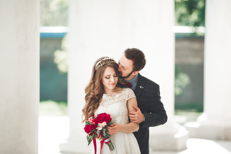 arm bouquet: Beautiful couple, bride and groom posing near big white column.