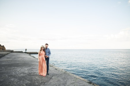 Bella coppia di innamorati, l'orgoglio con abito lungo a piedi sul molo.