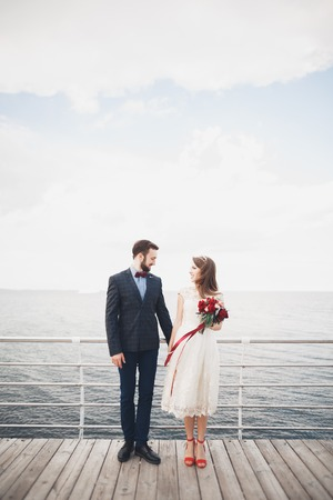 Married wedding couple standing on a wharf over the sea. Banque d'images
