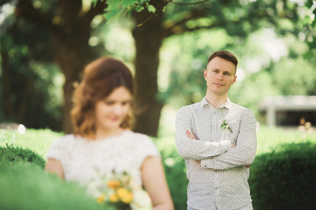 waits: Bride posing and smiles while groom waits on the background. Stock Photo