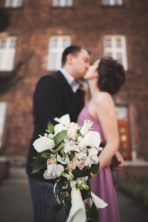 wedlock: Wedding flowers bouquet with newlywed couple on background. Stock Photo