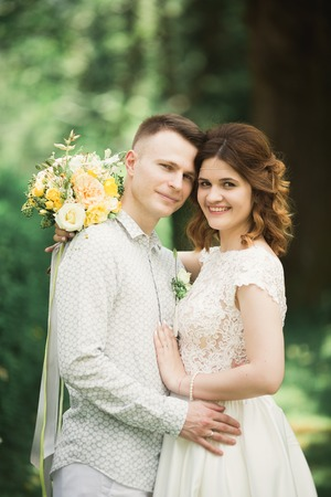 Stylish couple of happy stylish newlyweds walking in the park on their wedding day with bouquet.