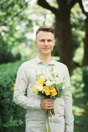 Man, groom posing with perfect wedding bouquet. Stock Photo
