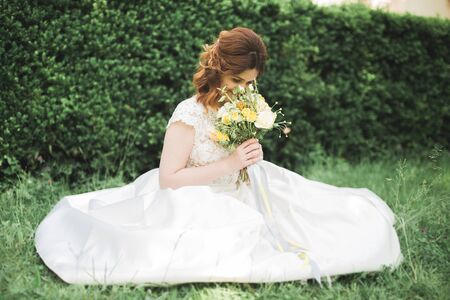 Lovely bride sitting on ground holding a bouquet smiling at camera. Stock Photo