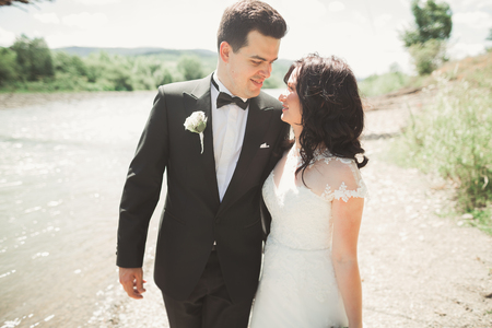 creating: Elegant gentle stylish groom and bride near river with stones. Wedding couple in love.