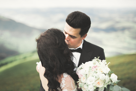 Beautifull wedding couple kissing and embracing near mountain with perfect view. Banque d'images