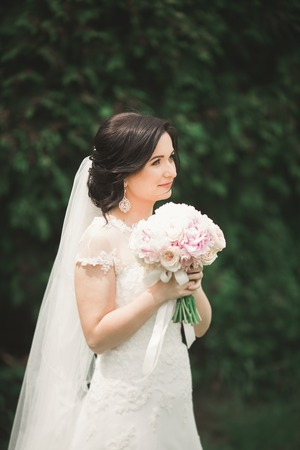 Beautiful brunette bride in elegant white dress holding bouquet posing neat trees.