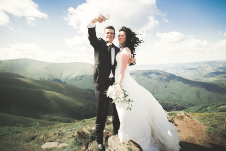 Just married couple on top of the mountain taking selfie picture.