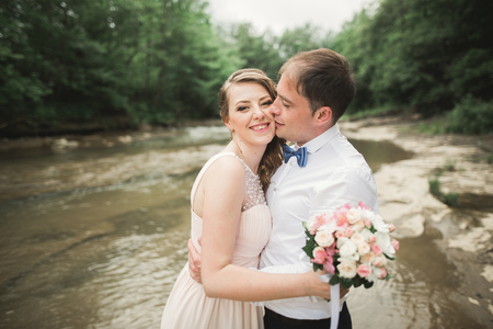 elegant stylish happy brunette bride and gorgeous groom on the background of a beautiful waterfall in the mountains.